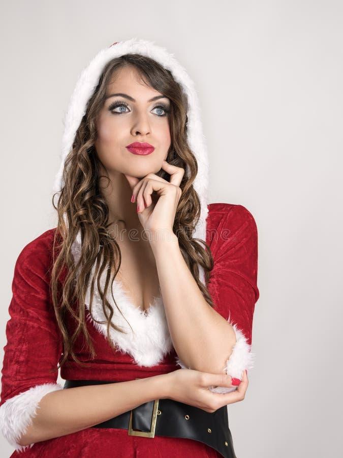 Eftertänksam tänkande ung jultomtenkvinna som ser upp med hoodien arkivbilder