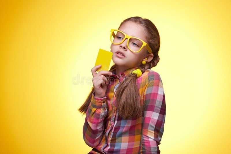Eftertänksam tonårig flicka med kreditkorten över gul bakgrund fotografering för bildbyråer
