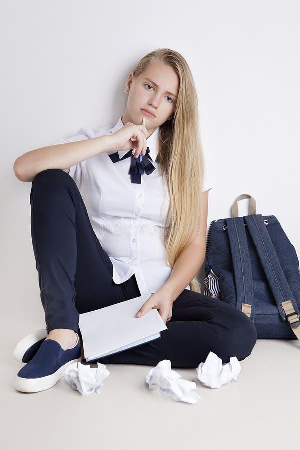 Eftertänksam tonårs- flicka med pennan i handsammanträde på golv arkivfoton