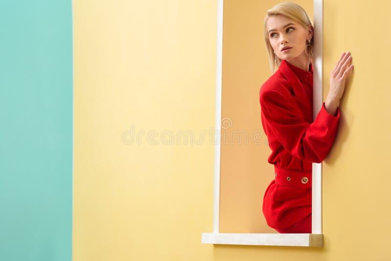 eftertänksam trendig kvinna i den röda dräkten som ut ser arkivfoton