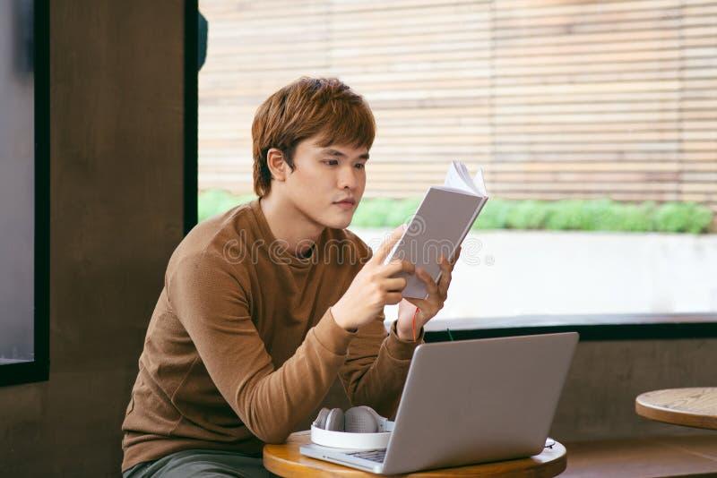 Eftertänksam ung asiatisk affärsmanläsebok på skrivbordet med varven royaltyfri bild