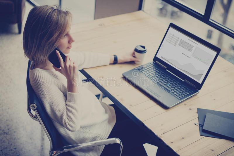 Eftertänksam ung kvinna som använder den moderna mobiltelefonen och bärbara datorn, medan sitta på trätabellen i coworking studio royaltyfria foton