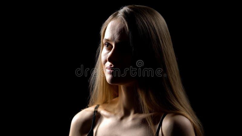 Eftertänksam ung kvinna som isoleras på mörk bakgrund, självkänslaproblem, komplex royaltyfria bilder