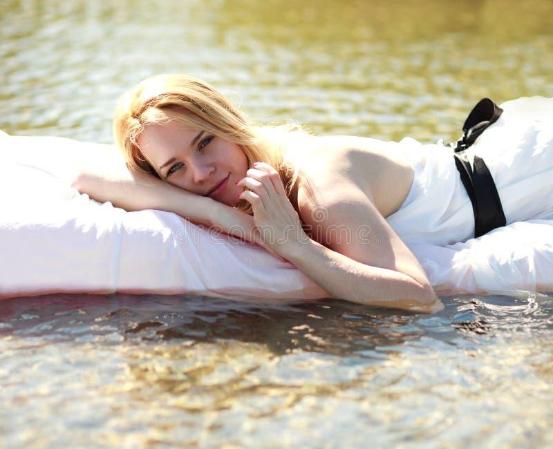 Eftertänksam ung kvinna som utomhus kopplar av i säng på vatten royaltyfria bilder