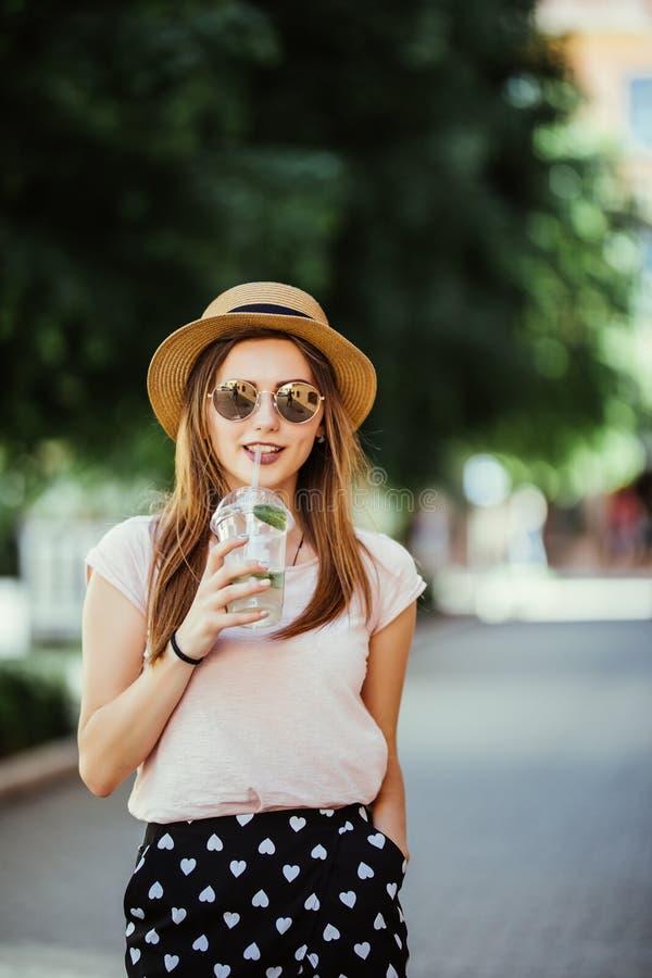Eftertänksam ung lycklig kvinna som utomhus läppjar en mojito i gatan arkivbild