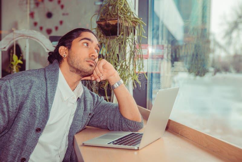 Eftertänksam ung man framme av bärbara datorn som ser för att sid fundersamt royaltyfria bilder