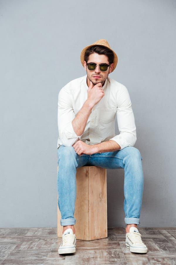 Eftertänksam ung man i solglasögon som sitter och tänker arkivfoto