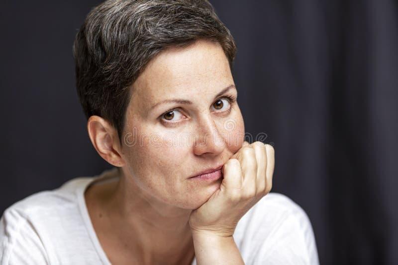Eftertänksam vuxen kvinna med kort hår svart st?ende f?r bakgrund N?rbild royaltyfri fotografi