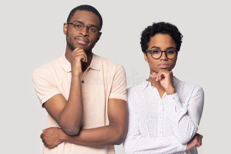 Eftertänksamma etniska par i exponeringsglas som tänker göra beslut royaltyfri bild