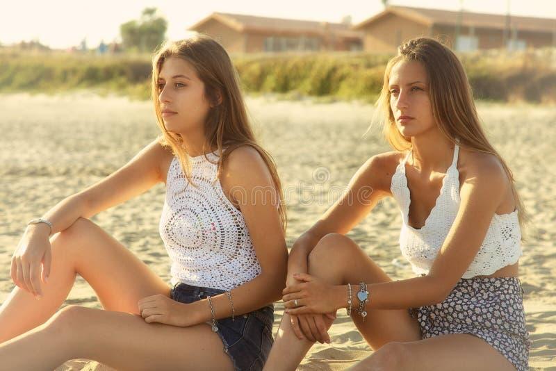 Eftertänksamma unga kvinnliga tonåringar som sitter på stranden på solnedgången arkivfoto