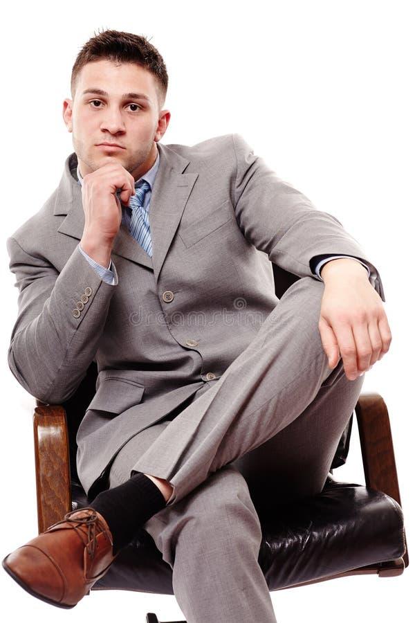 Eftertänksamt affärsmansammanträde på en stol med handen på hakan royaltyfri bild