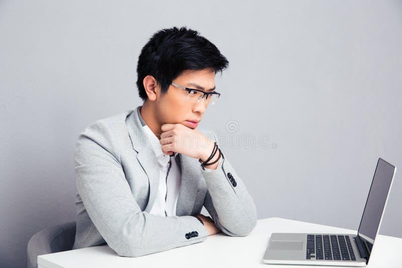 Eftertänksamt affärsmansammanträde på tabellen med bärbara datorn arkivbild
