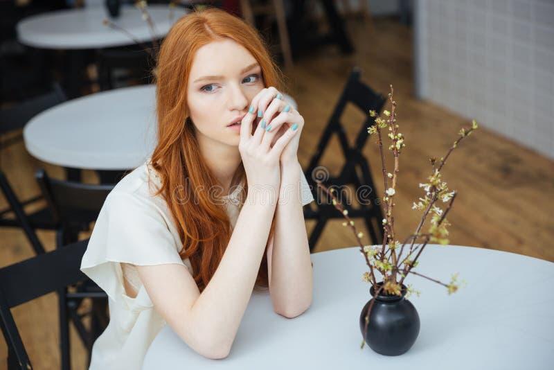 Eftertänksamt attraktivt sammanträde för ung kvinna på tabellen i kafé arkivfoto