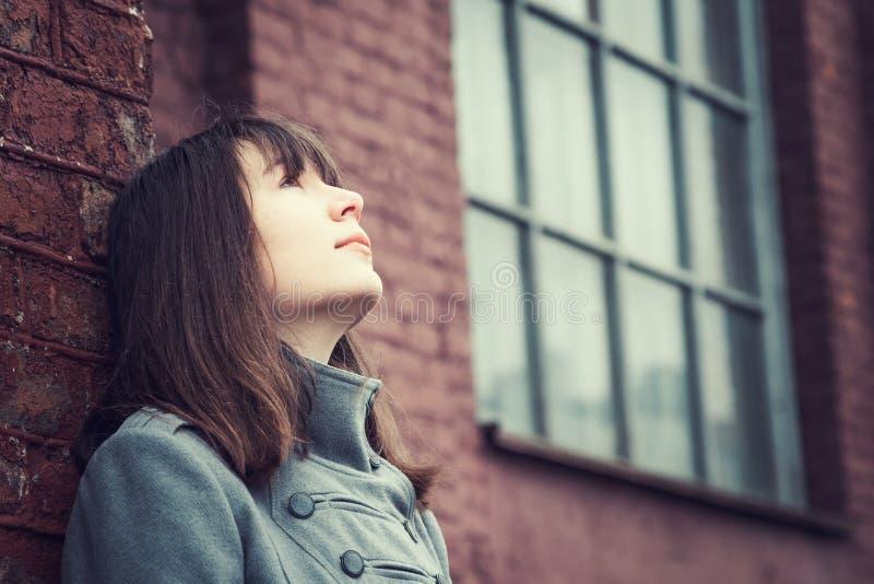 Eftertänksamt härligt ung flickaanseende nära en tegelstenvägg arkivbilder