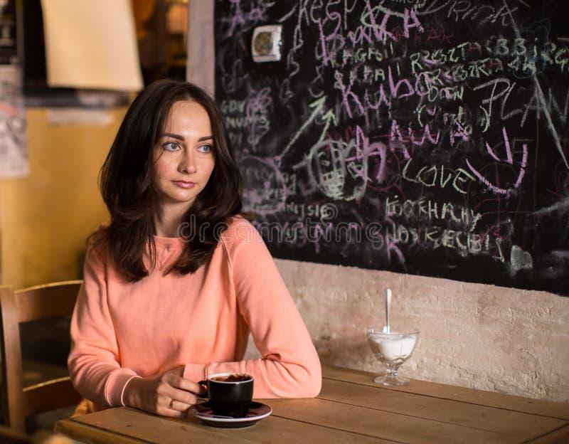 Eftertänksamt kvinnasammanträde i ett kafé arkivfoton