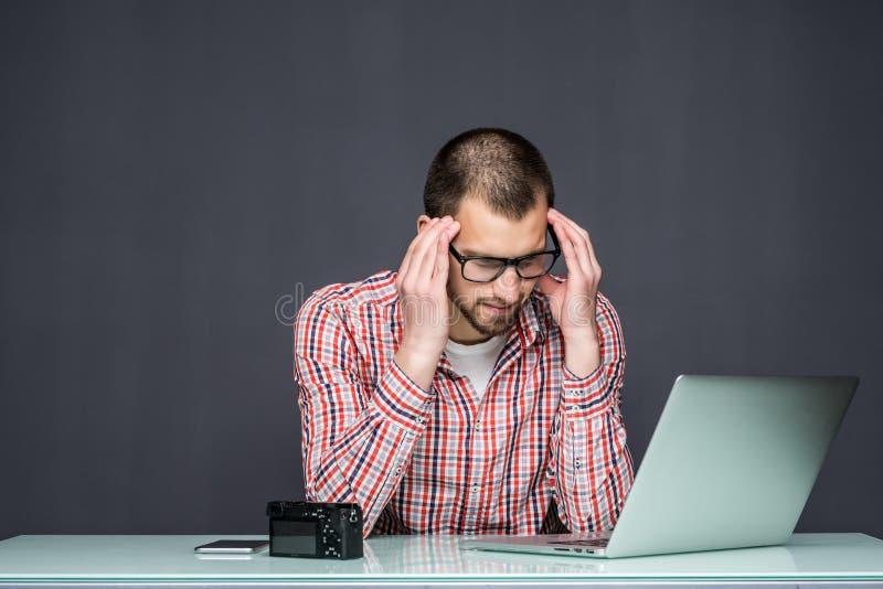 Eftertänksamt ledset mansammanträde på tabellen med bärbara datorn över grå bakgrund arkivbild