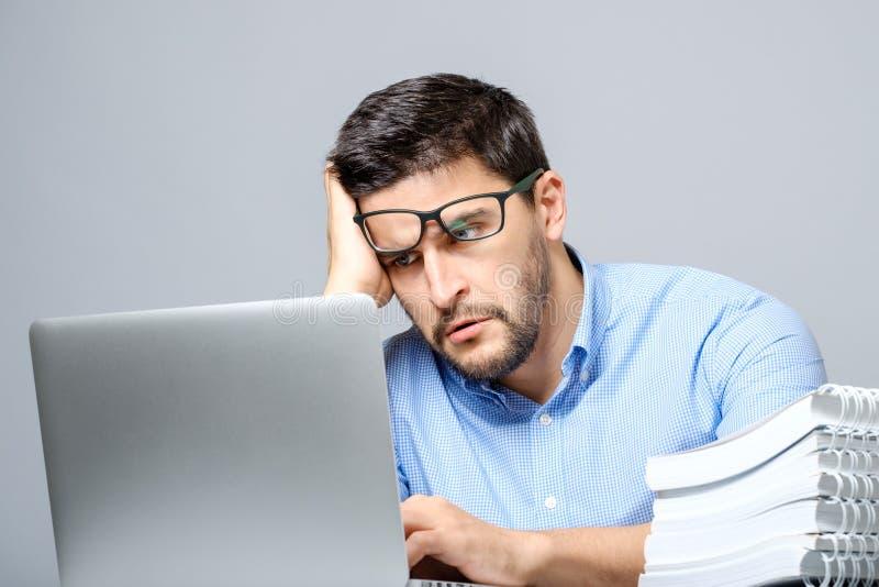 Eftertänksamt ledset mansammanträde på tabellen med bärbara datorn arkivbild