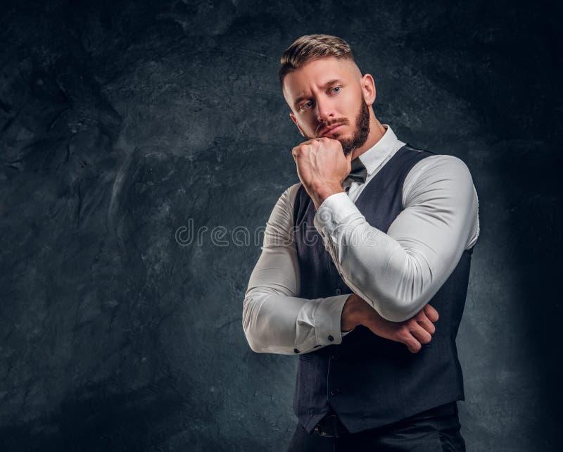 Eftertänksamt manligt tänka omkring något som är viktig Elegantly ung man för påklädd i en väst med flugan som poserar med handen royaltyfri foto