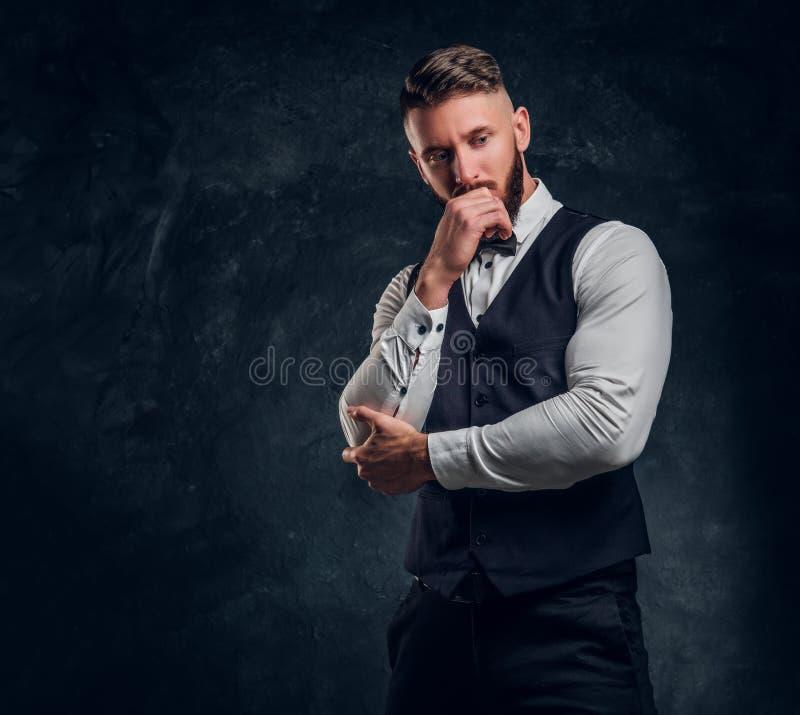 Eftertänksamt manligt tänka omkring något som är viktig Elegantly ung man för påklädd i en väst med flugan som poserar med handen royaltyfria bilder