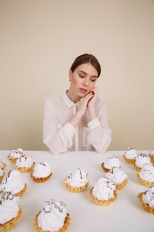 Eftertänksamt nätt sammanträde för ung kvinna på tabellen med kakor royaltyfri foto