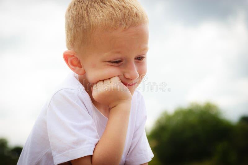 Eftertänksamt pojkebarn som tänker och dagdrömmer fotografering för bildbyråer