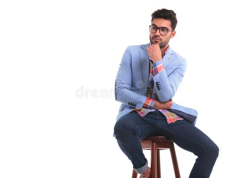 Eftertänksamt sammanträde för ung man på en stol royaltyfria bilder