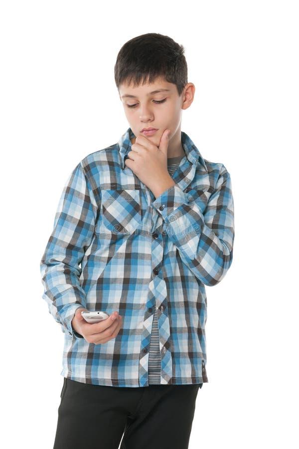 Eftertänksamt tonårigt med en mobiltelefon royaltyfria bilder