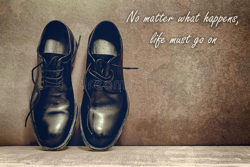 egal was geschieht, muss das Leben weitergehen, braunes Brett und Arbeitsschuhe auf Bretterboden lizenzfreies stockbild