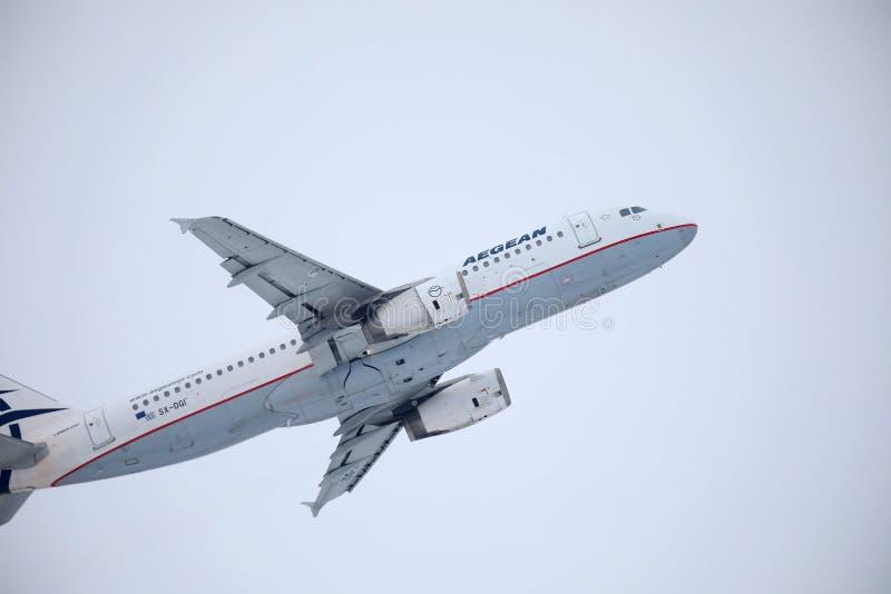 Egeïsch luchtvaartlijnenvliegtuig die over de Luchthaven van München, Duitsland vliegen stock afbeeldingen