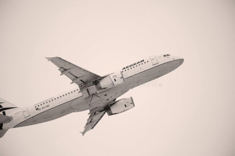 Egeïsch luchtvaartlijnenvliegtuig die over de Luchthaven van München, Duitsland vliegen stock fotografie