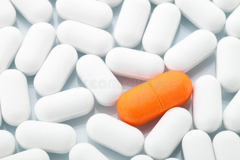 Orange pill mellan vit en arkivbild