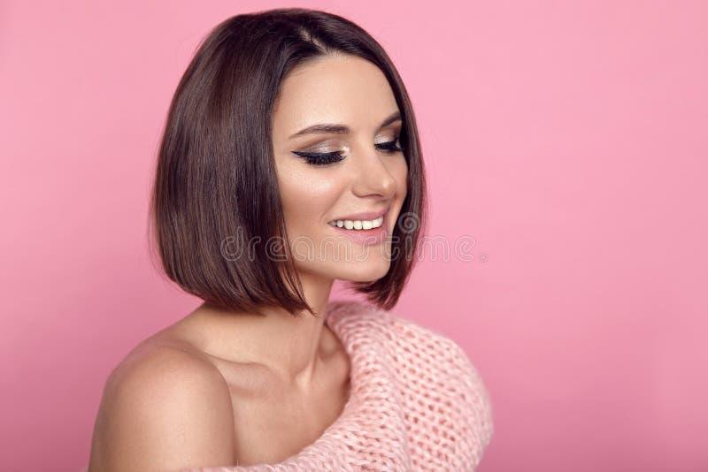 Egennamnfrisyr Sexig flickamodell i trendiga woolen kofta- och behådamunderkläderställningar mot bakgrunden av en beige vägg royaltyfria bilder