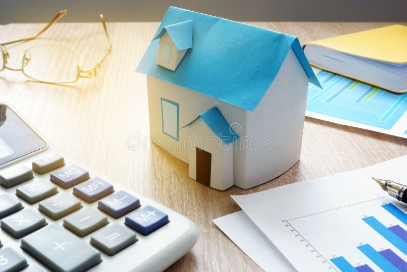 Egenskapen investerar modellen av huset och finansiell information om fastighetmarknad arkivfoto