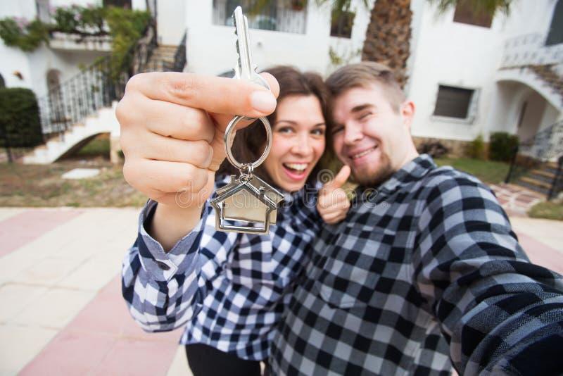 Egenskaps-, fastighet- och lägenhetbegrepp - lycklig rolig ung paruppvisning tangenter av deras nya hus royaltyfria foton