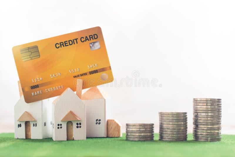 Egenskapsinvestering, miniatyrhusmodell med kreditkorten och pengarmyntbunt på simuleringsgräs, vit bakgrund arkivfoto