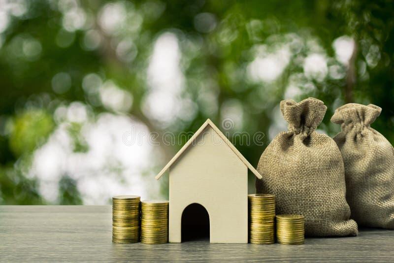 Egenskapsinvesteringen, bostadslånet, hus intecknar begrepp En modell för litet hus med bunten av mynt och pengarpåsen på trätabe arkivbild