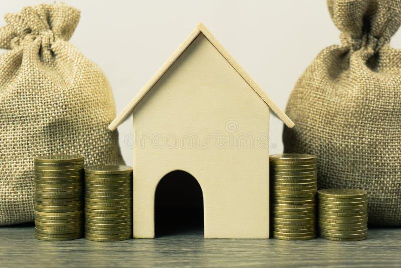Egenskapsinvesteringen, bostadslånet, hus intecknar begrepp En modell för litet hus med bunten av mynt och pengarpåsen på trätabe royaltyfria bilder