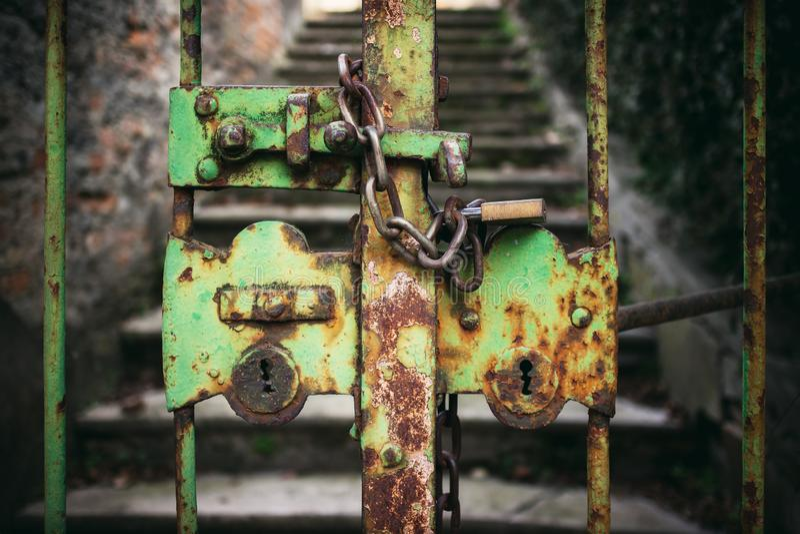Egentligen gammal, stängd och rostig grön järnport med kedjan och hänglåset royaltyfri fotografi