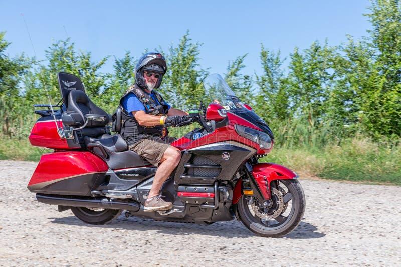 Senior motor biker Honda Goldwing making a drive through Hungary. Eger, Hungary - July 04, 2019: Senior motor biker with beard and short pants at yellow Honda stock photos
