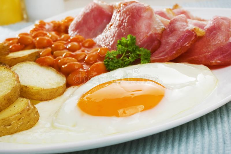 Egg and Bacon with Fried Potatoes and Baked Beans. English breakfast of bacon, fried egg, saute potatoes and baked beans royalty free stock photography
