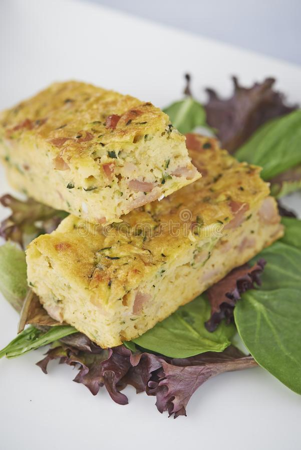 Egg and bacon quiche slices on lettuce stock images