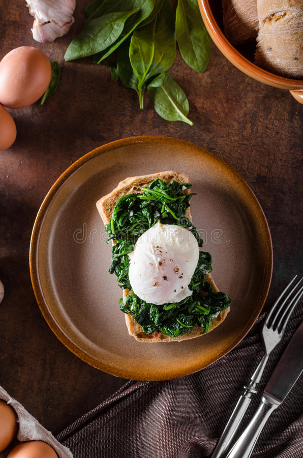 Egg benedict with garlic spinach. Toasted baquette royalty free stock photography