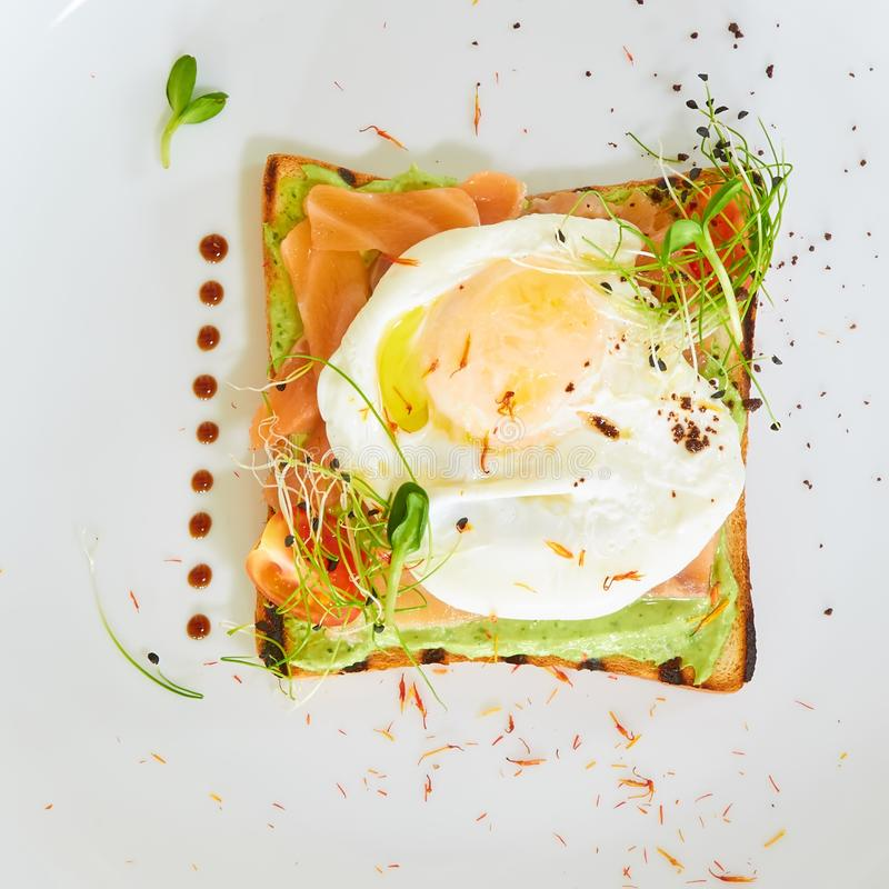 Egg benedict with hollandaise sauce and smoked salmon on toast. Delicious breakfast. stock photos