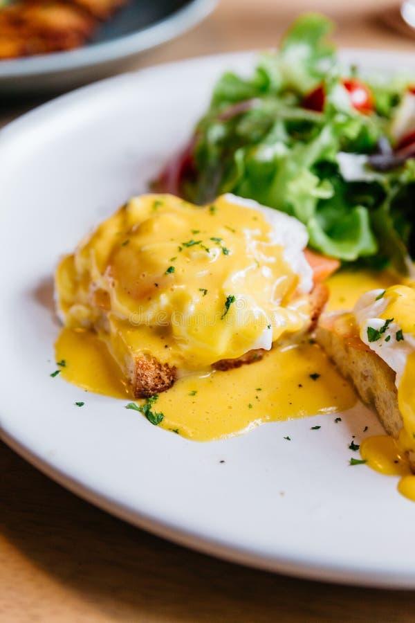 Egg a Benedicto servido con la ensalada en la placa blanca en la tabla de madera para el desayuno y el brunch deliciosos imagen de archivo libre de regalías