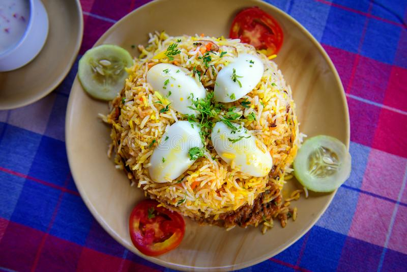 Egg Biryani - Basmati rice cooked with masala, eggs and spices, overhead view, close up. Egg Pilaf or Pulao served with vegetables stock photo