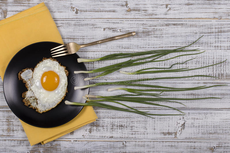 Egg , chives and black plate look like sperm competition, Spermatozoons floating to ovule in white wooden background. Egg , chives and black plate look like royalty free stock images