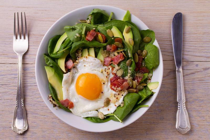 Egg com as sementes do quinoa, do abacate, do bacon, dos espinafres e de abóbora na bacia branca fotos de stock
