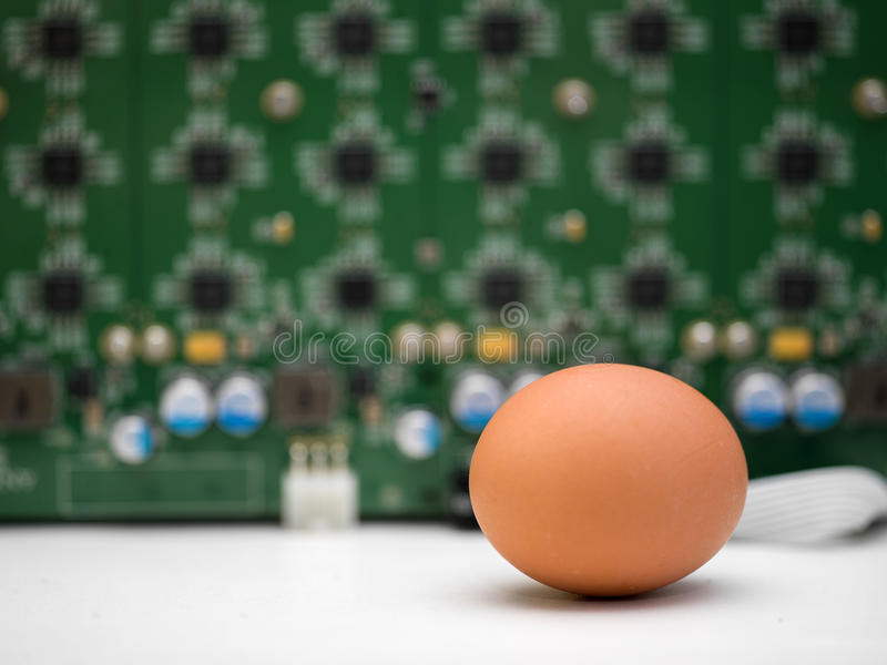 Egg And Computer. Front shot of an egg in the foreground and a computer processor in the blurred background. Concept of simplicity and complication in technology royalty free stock photography