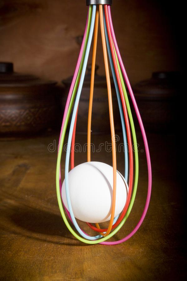 Egg in the culinary whisk. Egg in a culinary whisk on a wooden kitchen table stock images