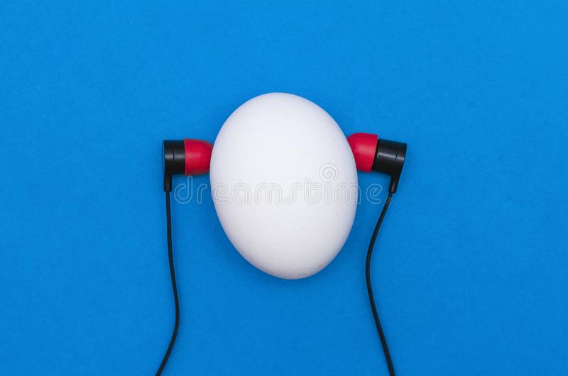 Egg. Easter concept. Chicken egg like a man head with earphones is listening a music isolated on the blue background, easter, song, headphones, singing royalty free stock photo